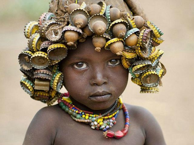 Eric Lafforgue «Niño corcholatas» El niño lleva muchos adornos en la cabeza y en el cuello