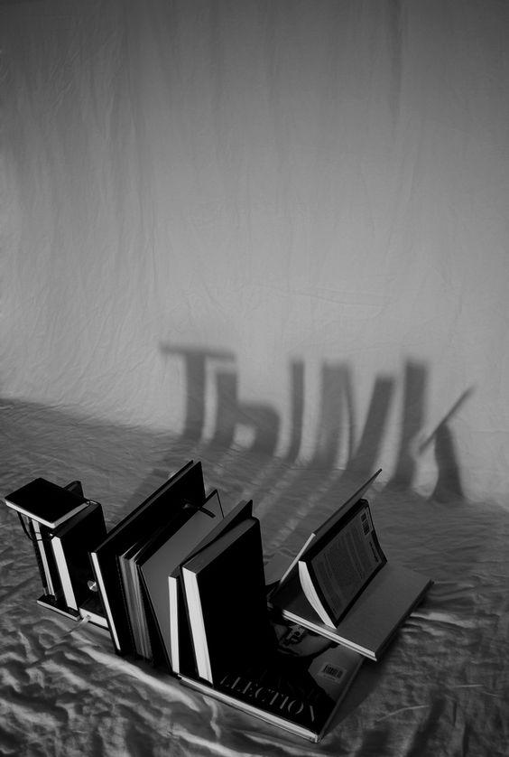 Thibodeau Photography «Think» Se ven unos libros en el suelo colocados de tal forma que en la pared se ve la sombra de la palabra think