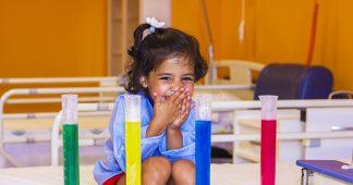 NIña riendo en el hospital detrás de unos tubos de ensayo con líquidos de colores