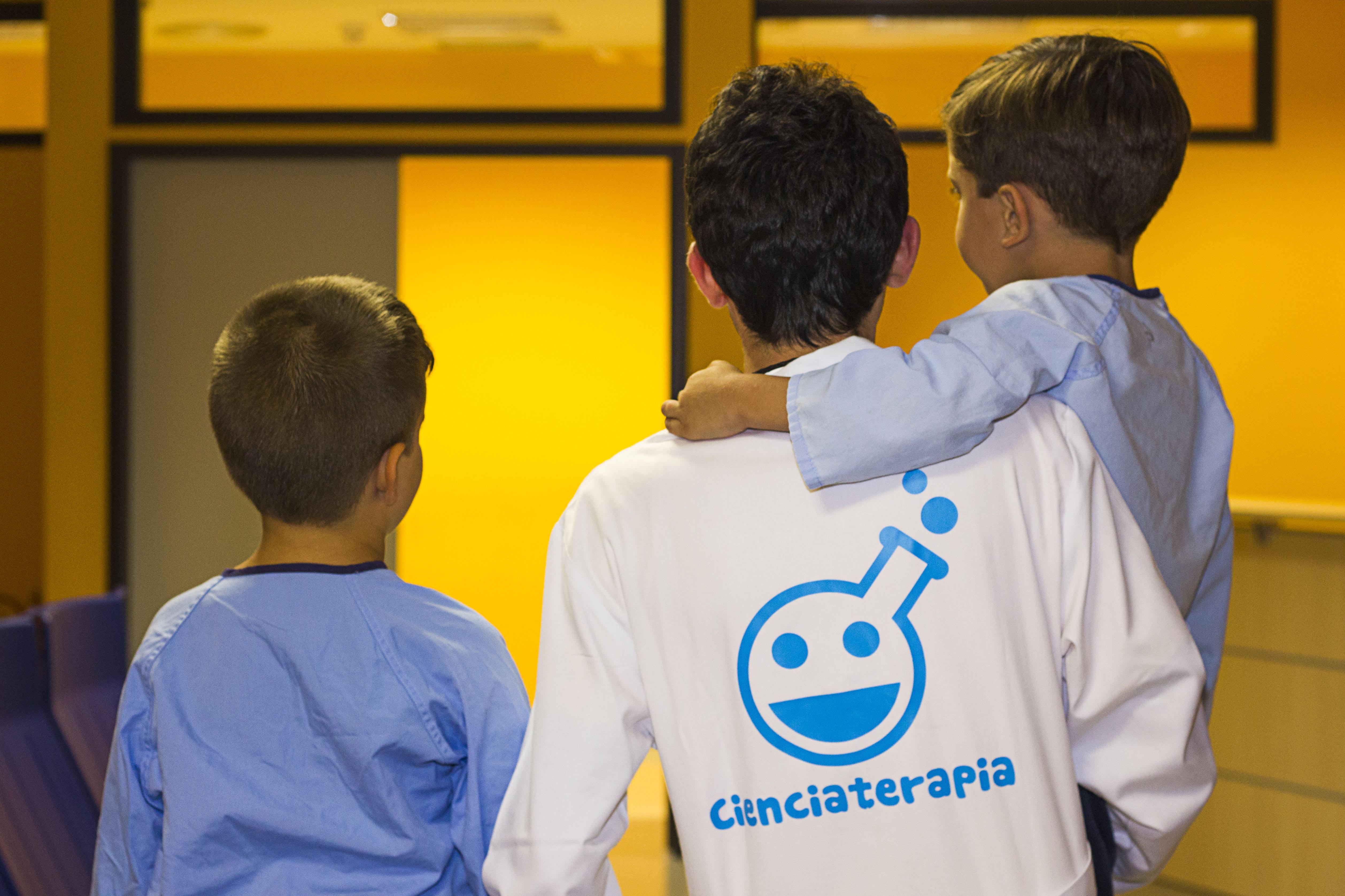 Cienciaterapeuta de espaldas con la bata que lleva el logo llevando a un niño en brazos