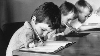 Niños con malformaciones en los brazos escribiendo.